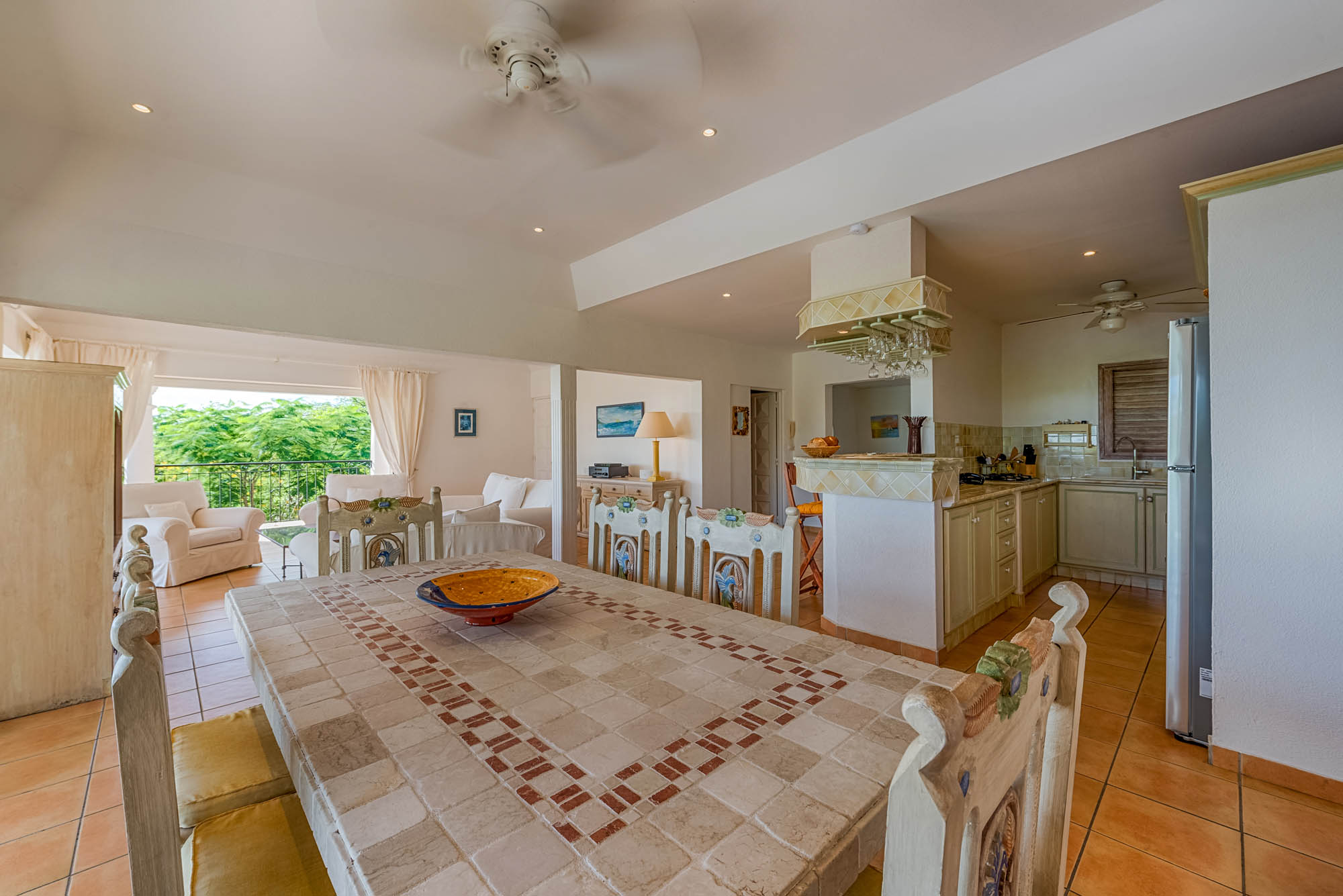 The large dining table of Little Provence villa rental, Baie Longue, Terres-Basses, Saint Martin, Caribbean is cooled by a ceiling fan.
