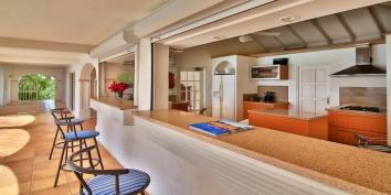 The modern, well equipped kitchen of Escapade villa features a pool-side bar and sea views.