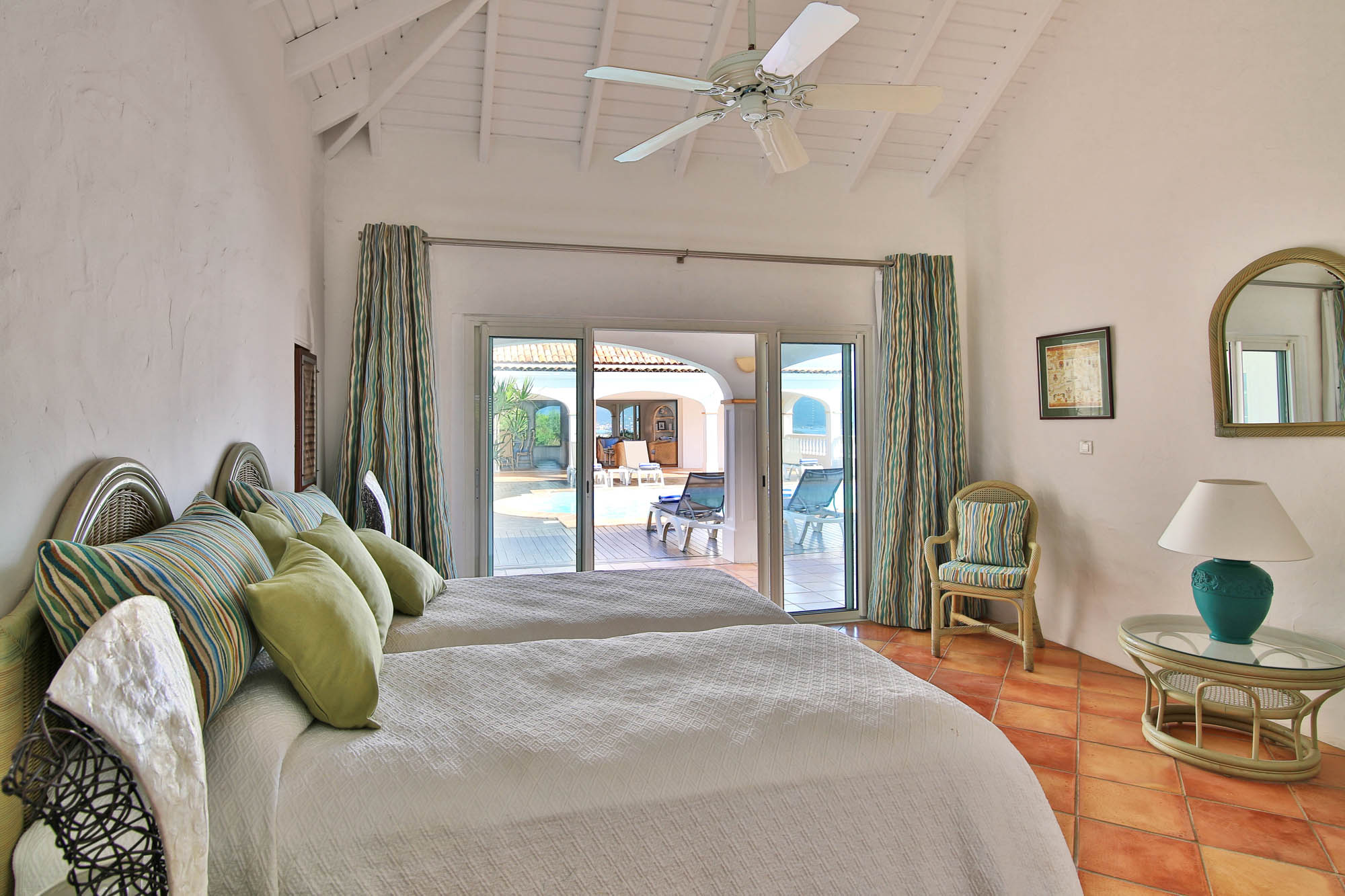 Three of the bedrooms in the main house of Escapade villa rental open directly onto the pool.