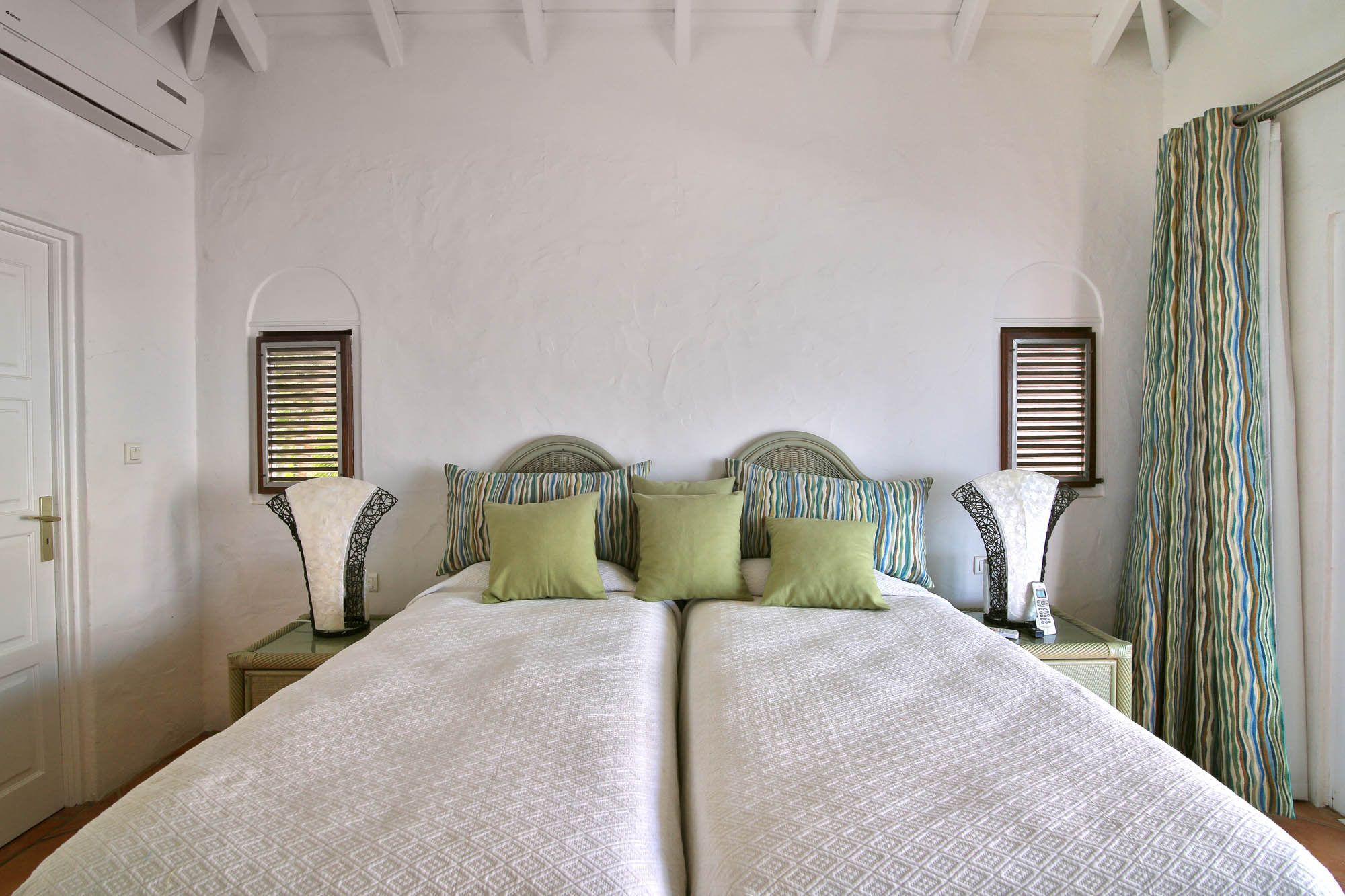 A photograph of one of the spacious bedrooms of this Caribbean holiday villa.