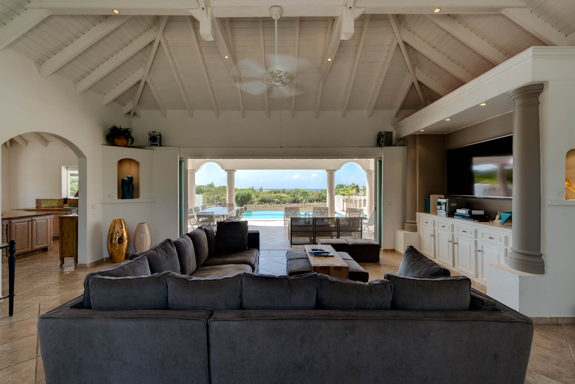 The comfortable living area of this Saint Martin vacation rental villa opens onto the terrace and a large gourmet kitchen that looks over the swimming pool.