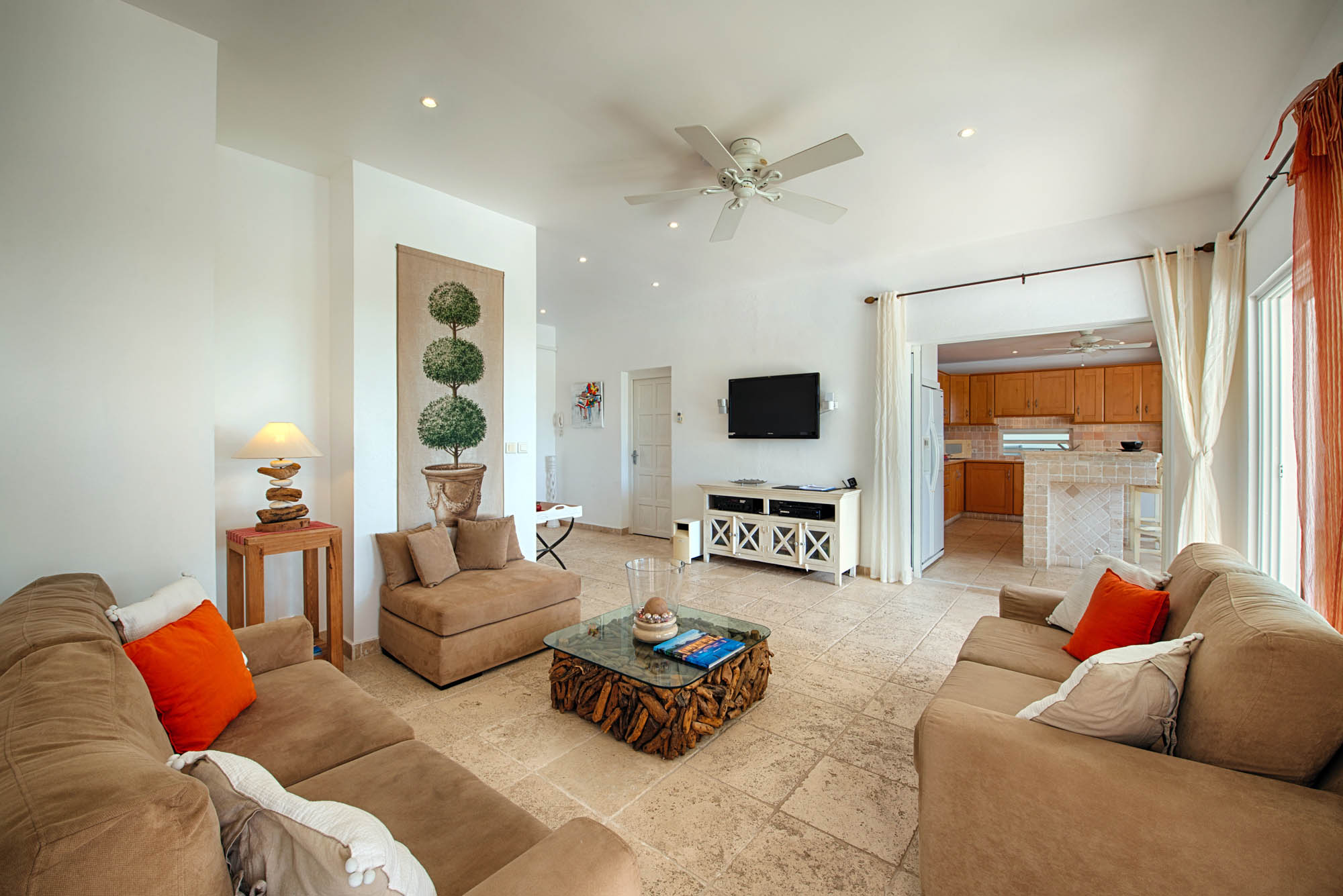 The living room of this Terres-Basses holiday villa rental features contemporary furniture, celing fans and a flat screen TV.