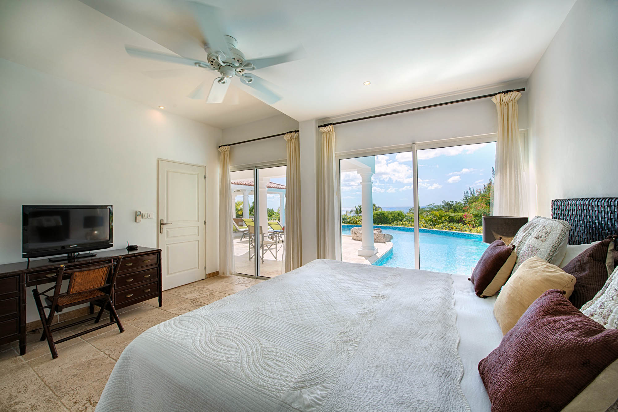 The guest bedroom of this Saint Martin villa rental opens to the living area and to the swimming pool.