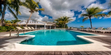 The large swimming pool and tropical palm trees at villa Eden, Long Bay Beach, St. Martin, French West Indies.