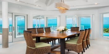 The indoor dining table of the Turks and Caicos villa rental comfortably seats 8 people.