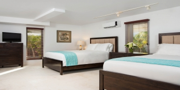 One of the beach level bedrooms with 2 queen beds at Beach Villa Sandstone, Providenciales (Provo), Turks and Caicos Islands.