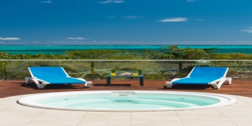 Relax in the Caribbean sun on the spacious deck or in the hot tub of this vacation villa rental in the Turks and Caicos Islands.