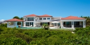 This Turks and Caicos vacation villa rental nestles amid lush tropical landscaping.