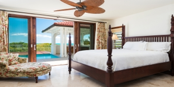 The master bedroom on the top floor of Dawn Beach Villa offers direct access to a private patio and outdoor bath tub.