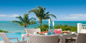 Enjoy alfresco dining with amazing views of world-famous Grace Bay at Turtle Beach Villa.
