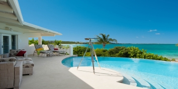 This Turks and Caicos luxury beach villa rental offers gorgeous views of Grace Bay from the swimming pool terrace.