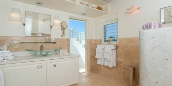The Seashell Room ensuite bathroom of Turtle Beach Villa, Turks and Caicos Islands, has direct access to a private outdoor shower.