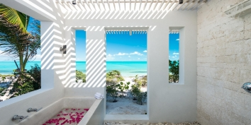 One of the master bedrooms at Aguaribay, Long Bay Beach, Providenciales features a modern outdoor bath and shower for perfect relaxation while on vacation.