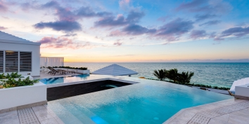 Enjoy beautiful sunsets from the infinity edge pool at this Turks and Caicos luxury villa rental.