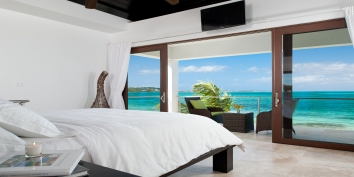 This Turks and Caicos luxury villa rental has a stunning master bedroom suite with fantastic views of the turquoise sea.