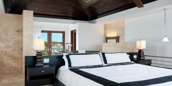 The master bedroom of Water Edge Villa has a king-size bed and en-suite bathroom, patio, large soaking tub, TV, and spectacular ocean views.