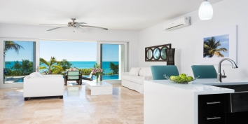 This Turks and Caicos beach villa rental has an open-concept kitchen and living room with great views of Sapodilla Bay.