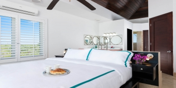 The upper level features two equal master bedroom suites with king beds and luxurious soaking tubs at Miami Vice Two, Providenciales, Turks and Caicos Islands.