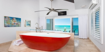 Soak in the luxurious bathtub while watching the sunset over the bay at this Turks and Caicos luxury vacation villa rental.