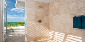 The master bedroom suites of this Turks and Caicos beach villa rental have indoor and outdoor bathrooms.