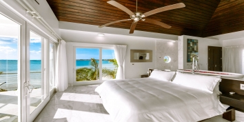 The master bedroom suite of this Turks and Caicos beach villa rental has two walls of glass doors to take advantage of the stunning views.