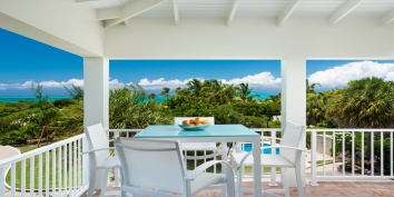 Dine on the covered porch and enjoy the views of the turquoise sea at this Providenciales villa rental.