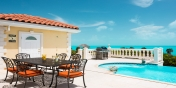 The infinity edged swimming pool and pool house at villa Sandy Beaches, Long Bay Beach, Providenciales (Provo), Turks and Caicos Islands.