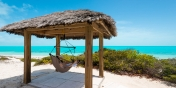 This Turks and Caicos villa rental has a beachfront tiki-hut with hammock chair.