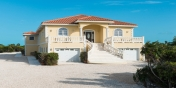 This Turks and Caicos holiday villa has plenty of parking space and you can watch the sun set from the porch.