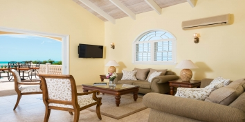 The upper level living room opens on to the pool deck at villa Sandy Beaches, Long Bay Beach, Turks and Caicos Islands.