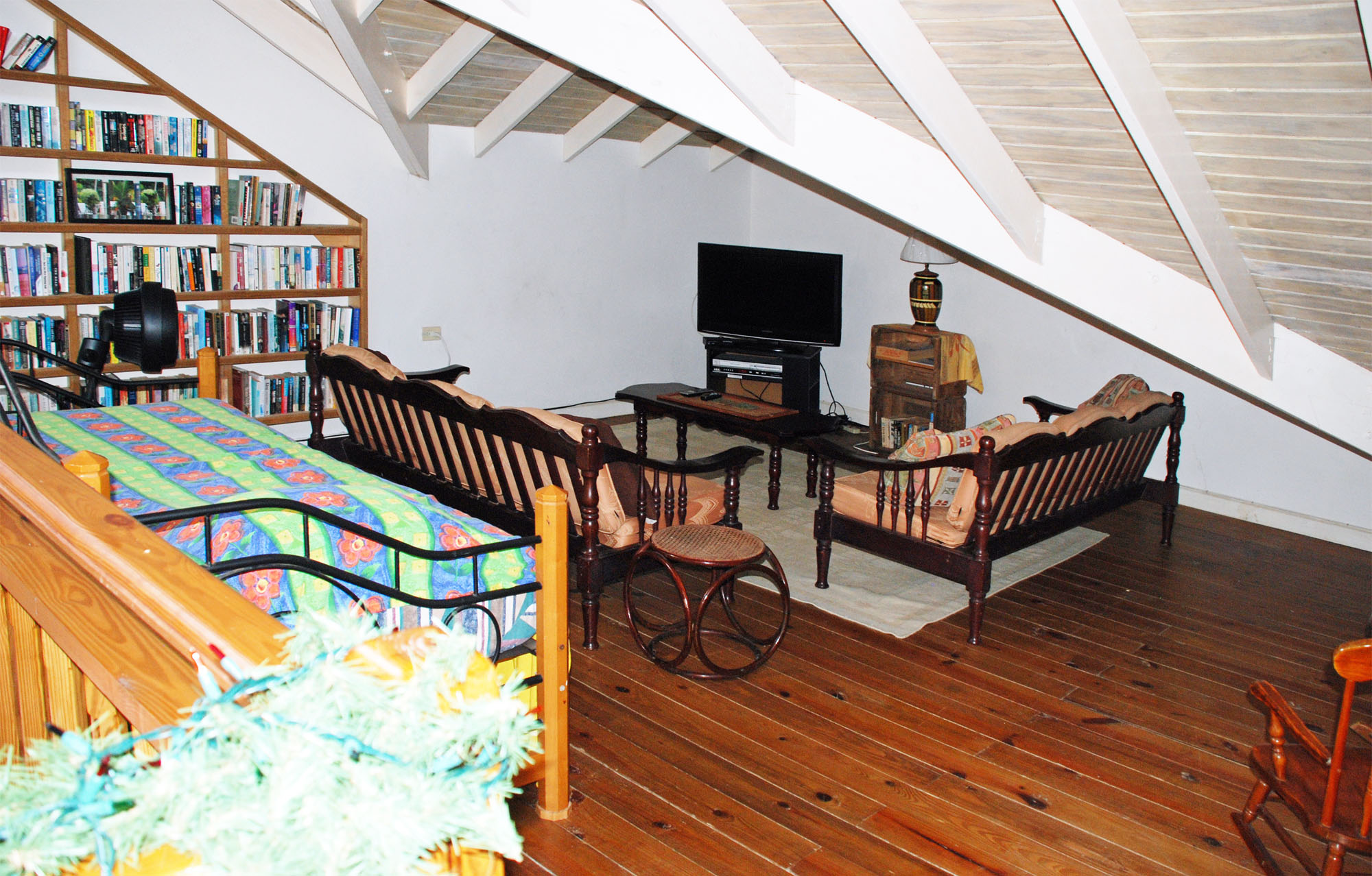 SOL Y MAR VILLA, TOBAGO W.I. Library loft with large selection of books on two walls, TV, and daybed