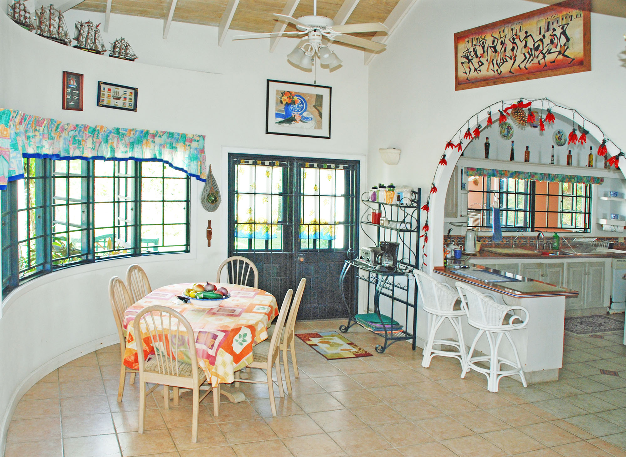 SOL Y MAR VILLA, TOBAGO W.I. Breakfast room + bar seating; arched entrance to the kitchen
