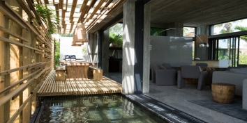 This Turks and Caicos luxury villa rental has a large timber dining table and reflection pool.