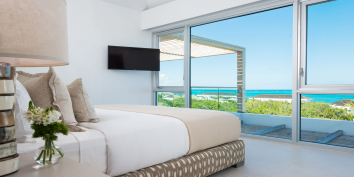 A guest bedroom with private bathroom and ocean view at Beach Enclave North Shore Villa 8.