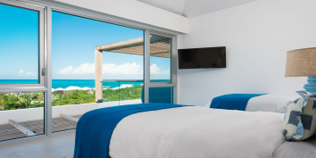 A guest bedroom suite with twin beds at Beach Enclave North Shore Villa 8, Providenciales, Turks and Caicos Islands.