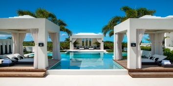 This Turks and Caicos luxury villa rental has cabanas and a pavillion around the swimming pool in the garden.