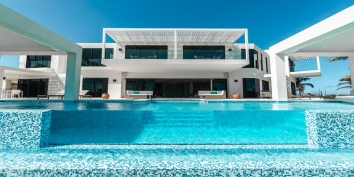 The beachside, swimming pool has a glass front at Triton Luxury Villa, Long Bay Beach, Providenciales (Provo), Turks and Caicos Islands, B.W.I.