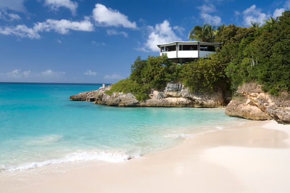 A house on a small cliff overlooking an uncrowded beach in Anguilla, Eastern Caribbean.
