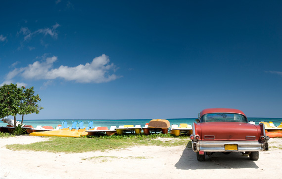 A classic car parked right next to the beach in Cuba, Caribbean.